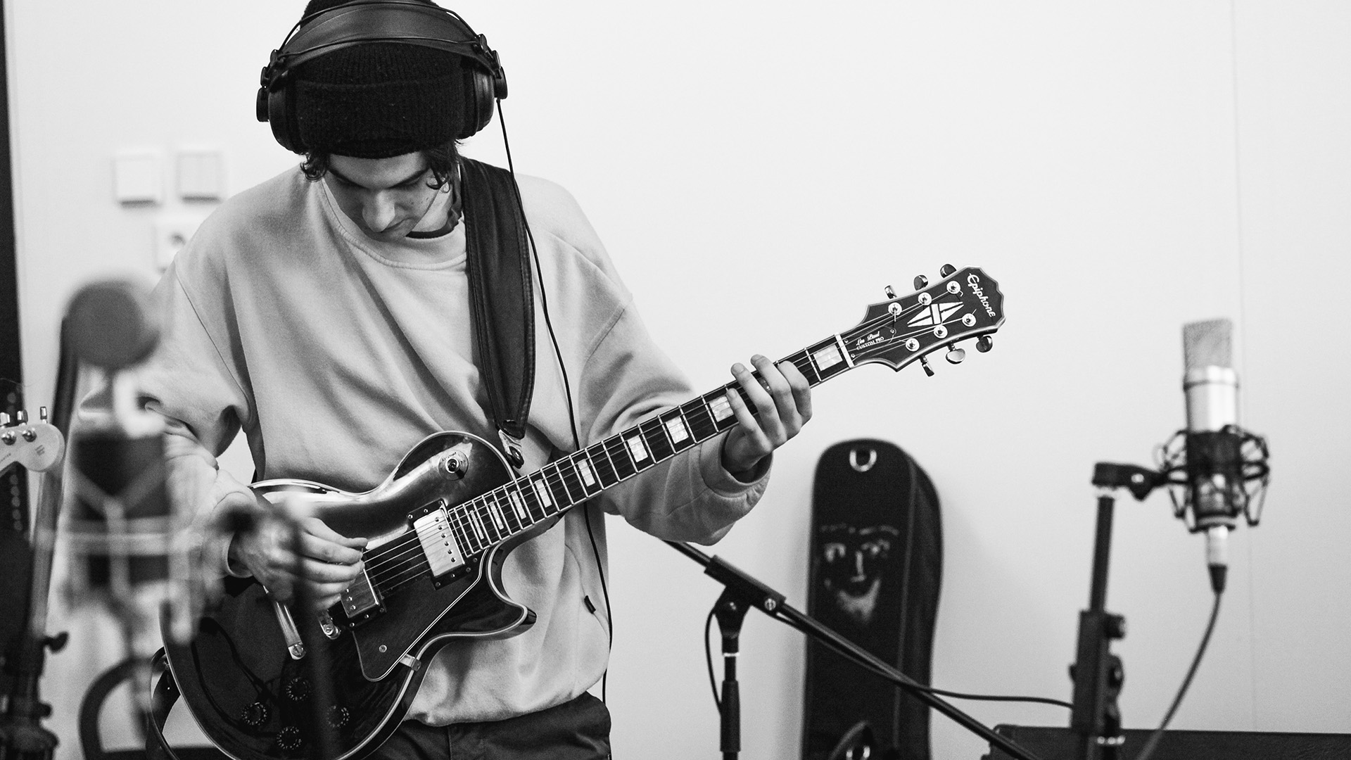 young guitarist recording his own song in a recording session