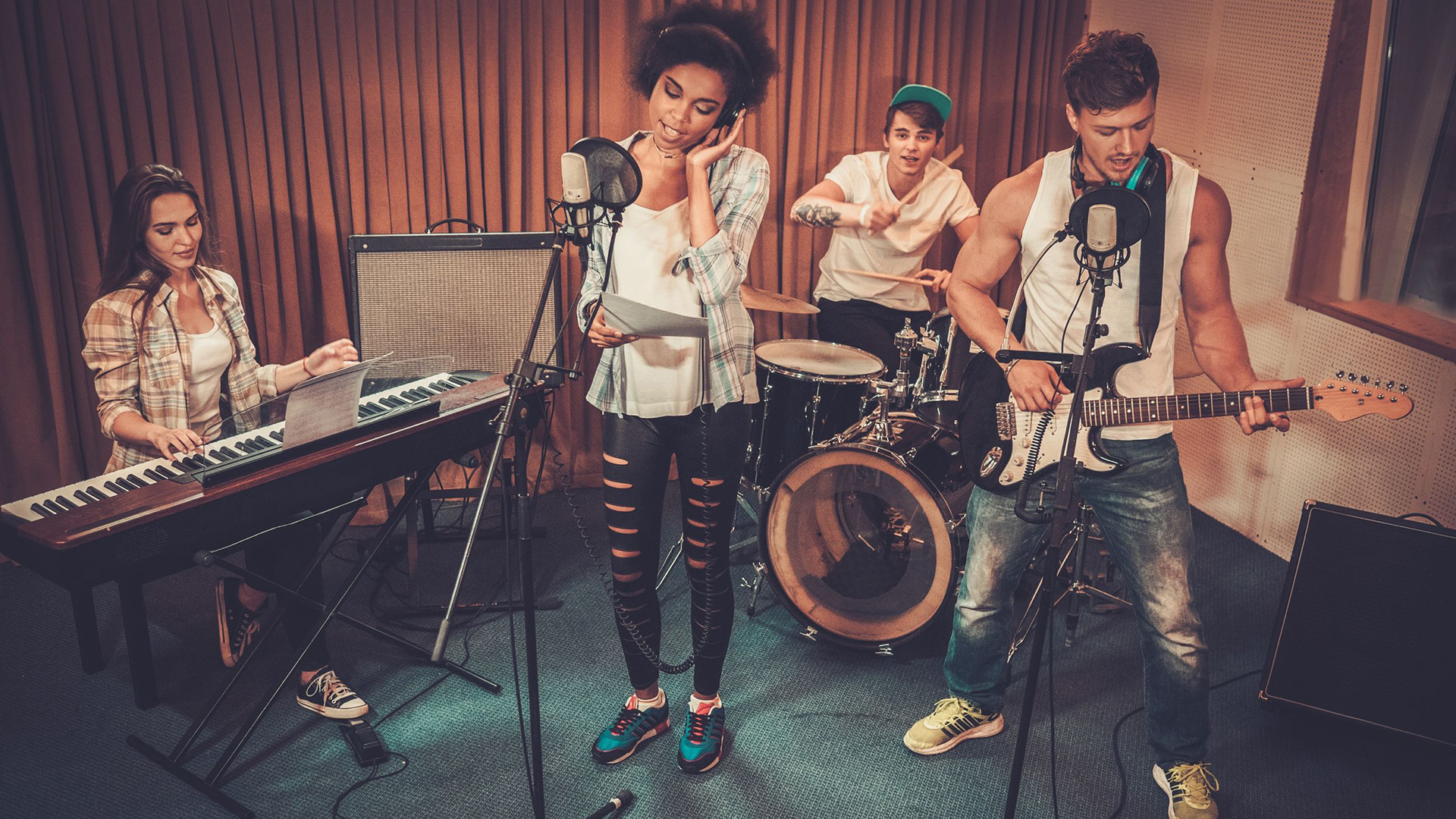 young band playing music with instruments and being recorded